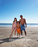 A family in a beach portrait while on vacation. Latino family, mom, dad, and young Boy